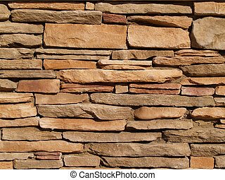 Flat, tan stones layered into a wall