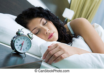 Image of alarm clock on background of sleeping female in the morning
