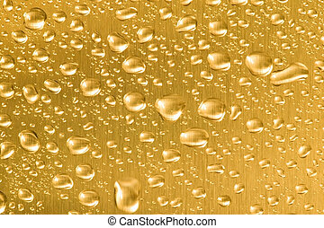 Gold metal with water droplets on.