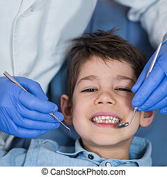 Dentist doing regular dental check-up to little boy.