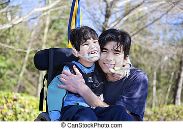 Little disabled boy in wheelchair hugging older brother outdoors, smiling together. Child has cerebral palsy.