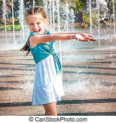 little girl in splashes a fountain