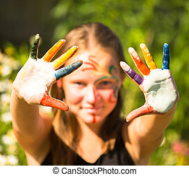 Little girl with hands in the paint.