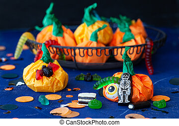 Little give away packages in shape of pumpkins, filled with sweets for Halloween