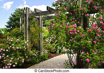 Lush green garden with stone landscaping, flowers, and arbor