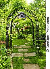 Lush green garden with wrought iron arbor