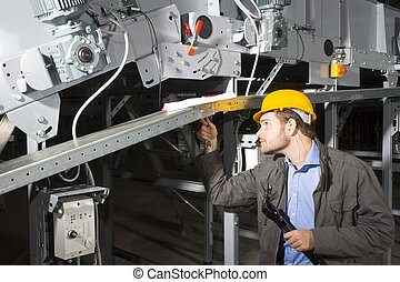 A maintenance engineer at work, tightening bolts of an industrial applience