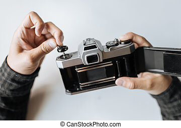 Male hand reloading film retro camera on a white table. Horizontal