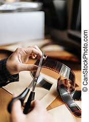Male hands cutting vintage film 35mm