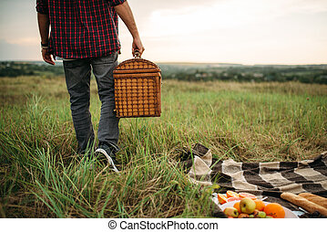 Male person with basket, picnic in summer field