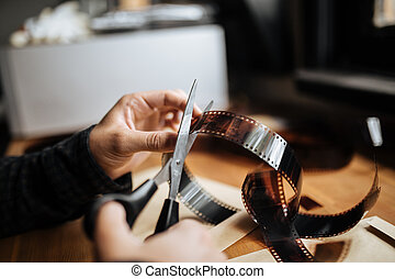 man cuts a 35mm film. Vintage, hipster, old