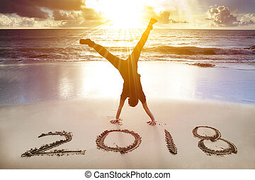 man handstand on the beach. happy new year 2018 concept