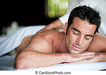 A good-looking man getting a back massage lying down