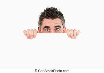 Man hiding behind white board