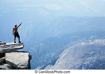 Man standing on top of a cliff with arm raised