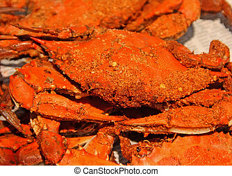 Traditional Maryland crabs steamed in Chesapeake bay seasoning served on top of newspaper spread over a table.