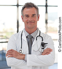 Potrait of a Mature senior Doctor in a hospital Smiling at camera