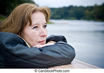 Portrait of attractive mature woman dreaming about something pleasant