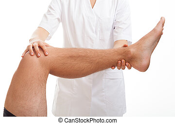 Doctor examining the injured leg in consulting room