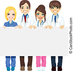 Group medical workers of doctors and nurses holding a blank billboard