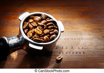 Metal espresso filter filled with rich brown fresh roasted coffee beans on a wooden surface with central highlight and stamped numbers