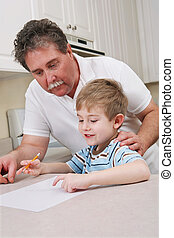 Middle aged father helping young son with homework