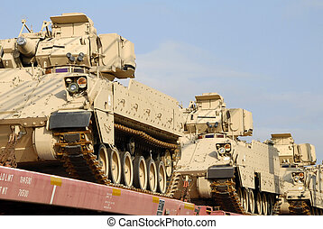 A freight train loaded with a shipment of military tanks