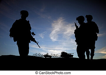 Modern day soldiers in Middle East silhouette against sunset sky with vehicles in background