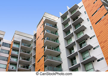 View of a modern residential apartment building, with blue sky in background
