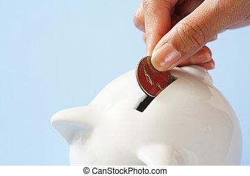 A woman saving a coin into a piggy bank