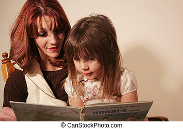 A mother and daughter are reading a book together.