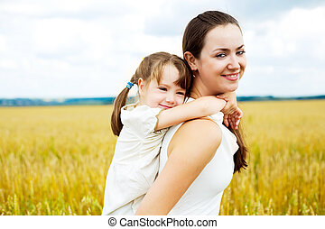 beautiful young mother and her daughter at the wheat field on a sunny day