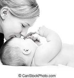 Happy mother kissing baby girl against white background