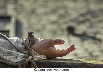 Hand nailed on wooden as reenactment of the crucifixion of Jesus Christ.