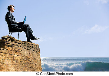 Image of confident business man sitting on the top of rock with laptop and looking at sea below