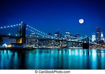 Night scene of the New York City's Brooklyn Bridge and Manhattan under a full moon