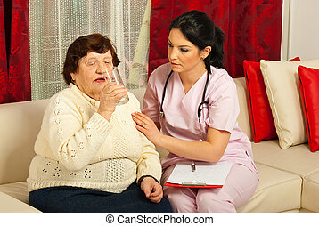 Nurse assist elderly woman drinking water at home