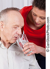 Nurse helping disabled man with drinking water