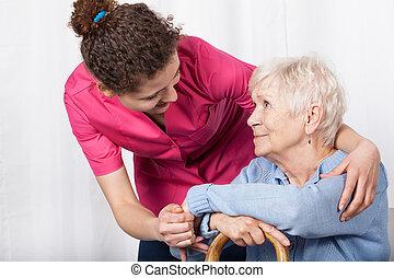 Nurse taking care of senior woman