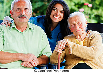 Happy group of people - doctor, carer, nurse with two patients in the garden of the nursing home.