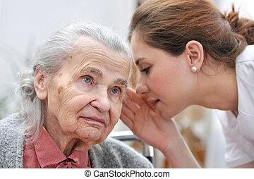 Female nurse is speaking in senior woman ear