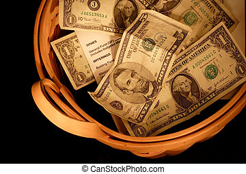 Closeup of a basket full of money and offering envelopes