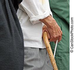 Old man holding onto his walking stick