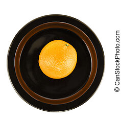 Fresh ripe orange on a black serving plate isolated in front of a white background.