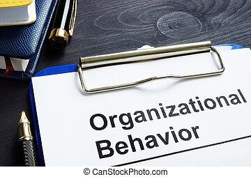 Organizational Behavior report on an office desk.