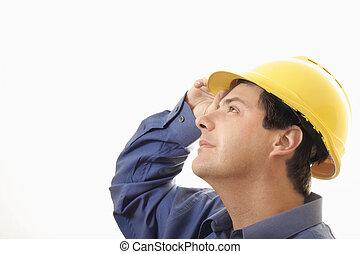 A man wearing hardhat looking upwards builder, mining, exploration, etc