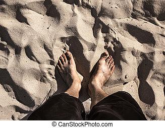 Pair of feet on beach sand