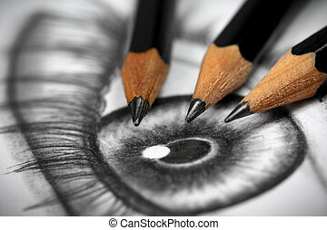 Close up of an eye drawing and three graphite pencils
