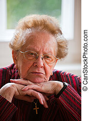An old woman sits thoughtfully at the window