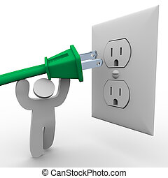 A person lifts a green electrical plug up to the power outlet